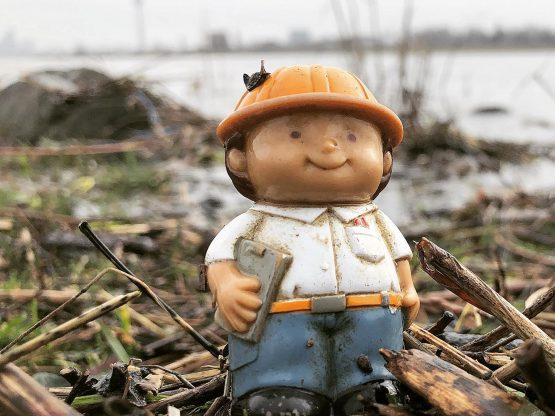 Dekoratives Bild: Spielzeugbauarbeiter aus Plastik an einem Fluss