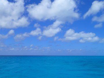 Dekoratives Bild: weiße Wolken über türkisfarbenem Meer